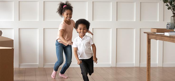 Imagem mostra uma menina correndo atrás de um menino em uma sala