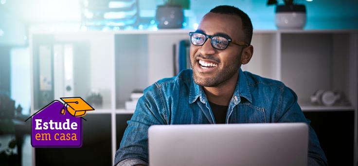 Homem de óculos está sorrindo sentado à frente de umcomputador para ilustrar pauta que traz uma lista de recursos digitais de aprendizagem para professores, estudantes e pais.