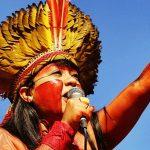 Célia Xakriabá é uma das lideranças indígenas que se destacam no Brasil. Ela está usando um cocar amarelo e laranja, além de pintura corporal enquanto fala ao microfone e gesticula com o braço esquerdo levantado.