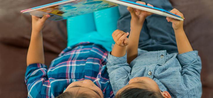 Duas crianças estão lendo deitadas, segurando um livro infantil acima de suas cabeças.