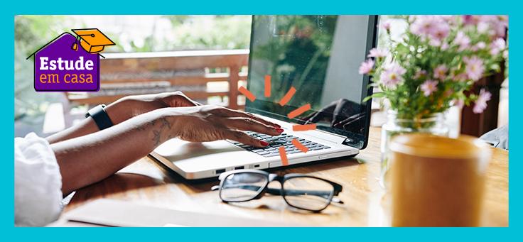 Imagem que ilustra o acesso a cursos a distância mostra uma mesa, em primeiro plano aparecem mãos femininas sobre o teclado de um notebook e um par de óculos ao lado.