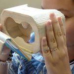 Imagem mostra moça usando óculos de realidade virtual feito de fibra de buriti durante aula