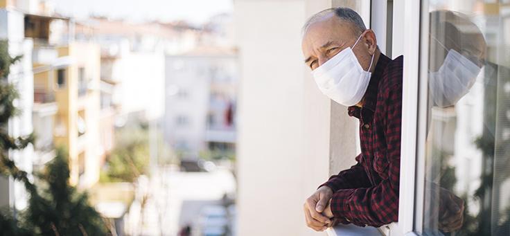 Imagem mostra um homem de máscara debruçado em uma janela, olhando para fora