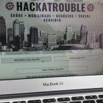 A imagem mostra o site do evento HackaTrouble, que uniu diversos profissionais em 48 horas de programação, em destaque na tela de um notebook.
