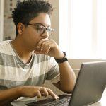 Imagem mostra um garoto olhando para um notebook com uma das mãos apoiada no queixo