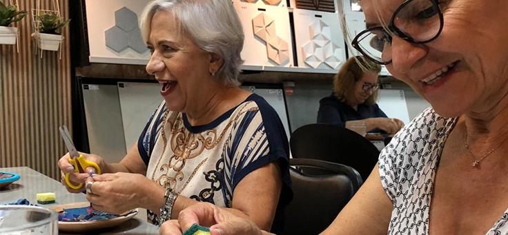 Imagem mostra duas mulheres sorrindo enquanto manuseiam alguns pedaços de pano