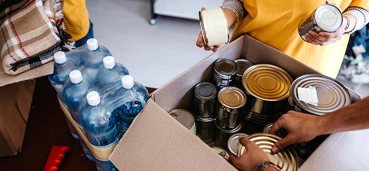 A imagem mostra mãos manuseando uma caixa de papelão aberta com latas de alumínio dentro e um engradado de garrafas de plástico ao lado