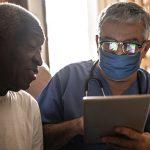 Imagem mostra um idoso sendo atendido na sala de casa por um médico de máscara e estetoscópio no pescoço