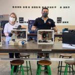 Quatro pessoas estão em sala de aula da ETEC de Pirsassununga ao lado de computadores feitos de peças de caça níqueis em projeto de tecnologia.