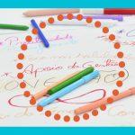 Imagem de um papel branco com diversos escritos coloridos e algumas canetinhas espalhadas