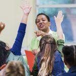 Imagem mostra uma mulher negra na frente de um grupo de jovens com a mão levantada