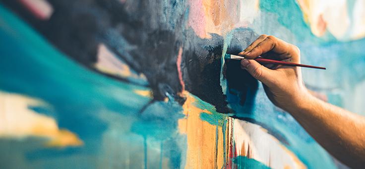 Imagem destaca uma mão segurando um pincel e pintando uma parede colorida