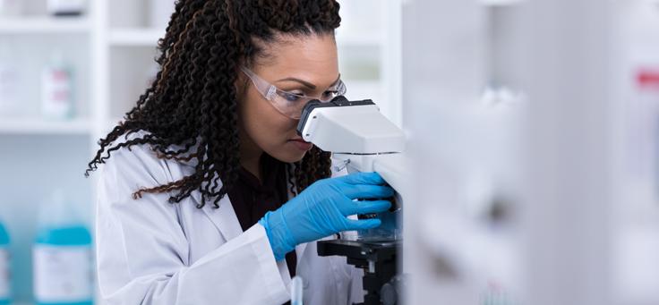 Imagem mostra uma mulher de jaleco e luvas olhando pela lente de um aparelho em um laboratório