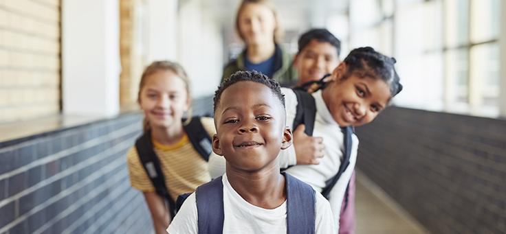Imagem mostra crianças sorrindo em uma fila