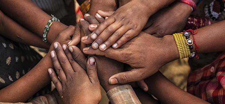 Imagem mostra várias mãos em destaque, uma em cima da outra