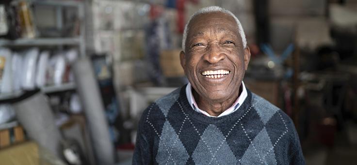A imagem mostra um homem idoso sorrindo