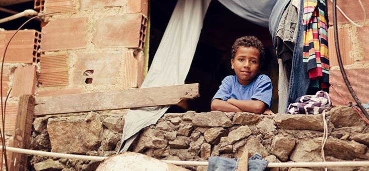 Imagem mostra uma criança olhando através de uma janela dentro de uma casa