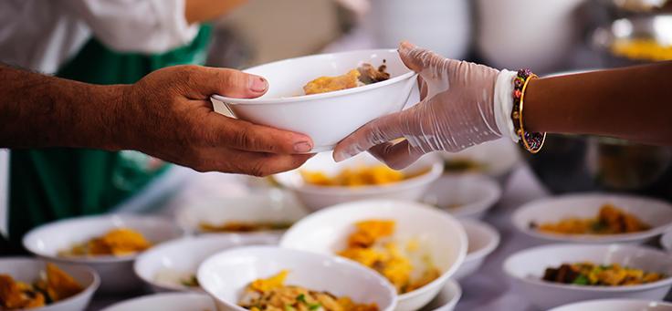 Imagem foca duas mãos no momento da entrega de uma marmita em ação de voluntários.
