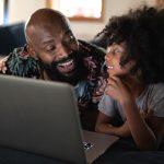Imagem mostra um pai e uma filha deitados olhando para um notebook e sorrindo