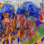 A imagem mostra quatro pessoas em uma rua vestindo trajes típicos de maracatu: que consistem em roupas bem coloridas e adereços grandes na cabeça