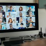 A imagem mostra uma pessoa de costas, sentada com fones de ouvido, olhando para a tela de um computador onde se vê o rosto de várias pessoas em uma videoconferência