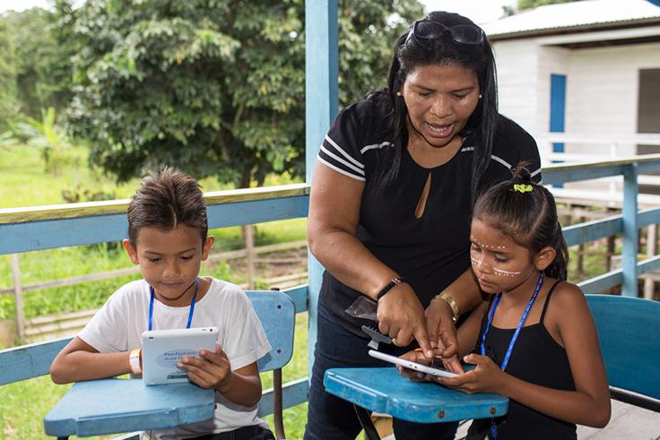 A imagem mostra duas crianças sentadas com tablets nas mãos e uma educadora, de pé, atrás de uma delas, apontando para a tela do aparelho