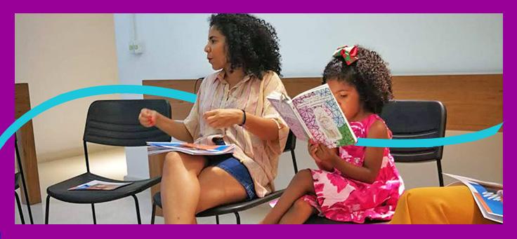 A imagem mostra a entrevistada Juliane Sousa em uma sala, sentada ao lado de uma criança que está lendo um livro.