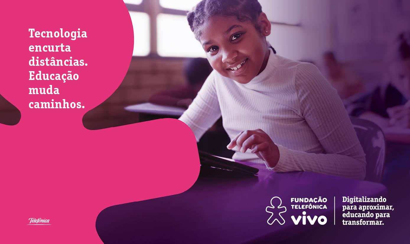 """Em imagem da campanha Educando para Transformar, menino em primeiro plano sorri sentado em carteira de escola com um tablet à sua frente. Ao fundo estão outras crianças. Ao lado esquerdo há o logo da Vivo com os dizeres: """"Tecnologia encurta distâncias. Educação muda caminhos.""""."""