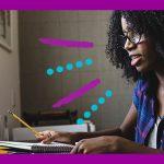 Para ilustrar pauta sobre saúde mental nas escolas, foto mostra mulher sentada diante da tela de um computador com a cabeça apoiada na mão esquerda. Ela está escrevendo algo em um caderno e está com o olhar perdido. Ela tem a pele negra, os cabelos encaracolados e está usando óculos.