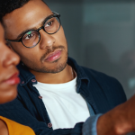 Imagem mostra dois jovens olhando para quadro com post-its para representar atividade em que é debatido o tema projeto de vida. O rapaz usa óculos e está apontando para o quadro, a mulher está com o rosto desfocado e olhando para onde ele aponta.