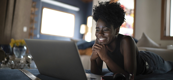 Imagem mostra uma jovem negra sorrindo com as mãos no queixo enquanto olha para a tela de um notebook