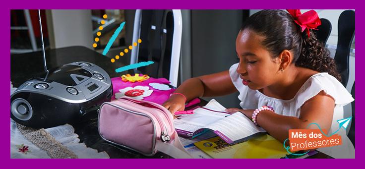 A imagem mostra uma criança dentro de casa, sentada atrás de uma mesa lendo uma material didático. Há também um rádio e um estojo escolar sobre a mesa.