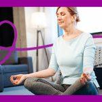 Imagem mostra um mulher em uma sala sentada no chão. Ela está com os olhos fechados e as pernas cruzadas com as mãos sobre os joelhos, em posição de meditação.