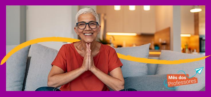 a imagem mostra uma mulher grisalha, de óculos de grau, sorrindo. Ela está sentada em um sofá com as pernas dobradas, os cotovelos apoiados sobre os joelhos e as mãos unidas em pose de meditação.