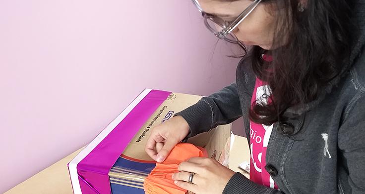 Lorena Carvalho, conhecida pelo canal Professora Coruja que foca em alfabetização e cultura digital, está de lado, colando um papel da cor laranja em uma caixa de papelão. Ela usa óculos e agasalho na cor cinza.