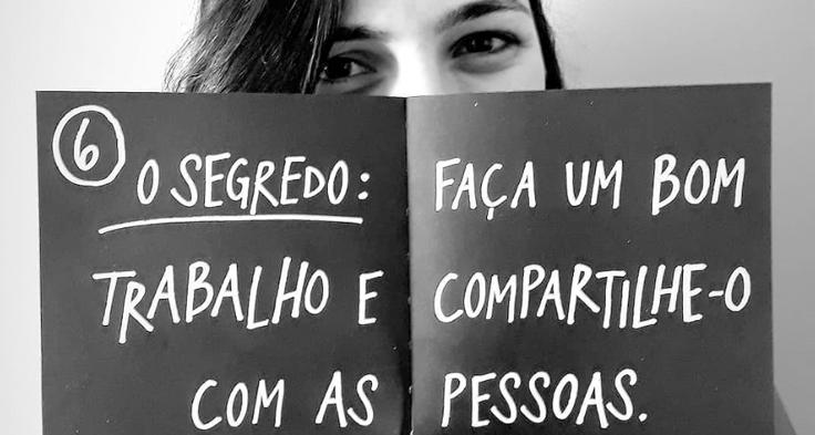 """Lorena Carvalho, conhecida pelo canal Professora Coruja que foca em alfabetização e cultura digital, segura um cartaz deixando apenas seus olhos à mostra. Há os dizeres: """"Faça um bom trabalho e compartilhe-o com as pessoas""""."""