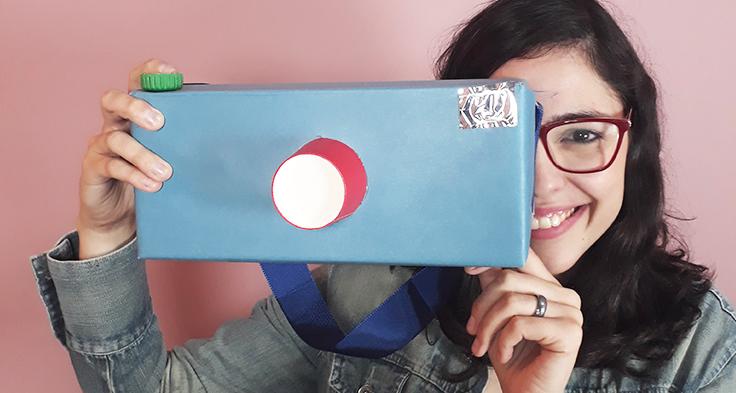 Lorena Carvalho, conhecida pelo canal Professora Coruja que foca em alfabetização e cultura digital, está segurando uma caixa de papelão encapada com papel colorido e simulando um modelo de câmera fotográfica.