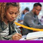 Imagem mostra uma jovem sentada em uma carteira na sala de aula. Ela está escrevendo em um caderno e há um livro aberto na sua frente. Ao fundo se vê uma imagem mais desfocada outros jovens sentados.
