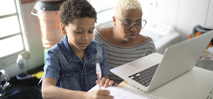 Mulher está olhando para tela de um notebook enquanto menino, ao seu lado, está escrevendo com uma caneta em um caderno. Imagem ilustra pauta sobre oficina que usou pensamento computacional para ressignificar relação com a cidade.