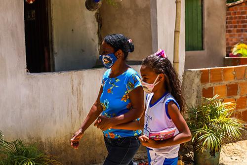 A imagem mostra uma senhora e uma criança de braços dados andando pela rua. Ambas estão com máscaras de proteção.