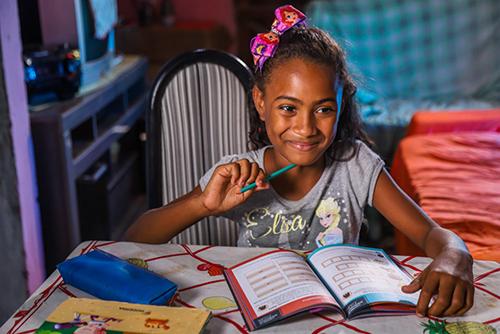 A imagem mostra uma menina sorrindo segurando um lápis e com um caderno a sua frente.