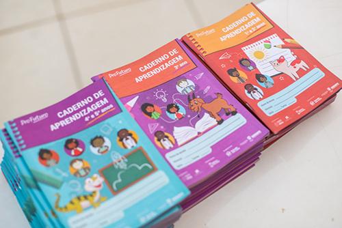 Imagem mostra os cadernos de aprendizagem do Projeto Aula Digital em destaque sobre a mesa