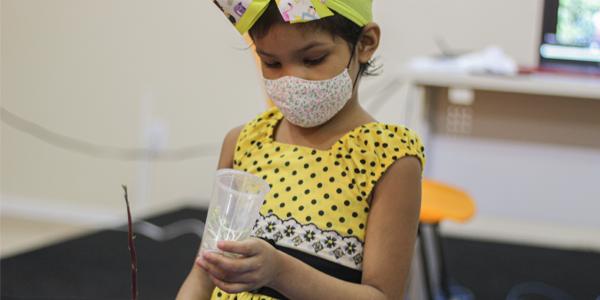 Menina usando máscara segura copo com muda de feijão em atividade na Associação Colorindo a Vida durante a Semana dos Voluntários.