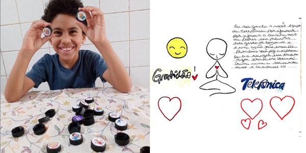 Menino aparece mostrando brinquedo feito durante oficina na Semana dos Voluntários. Ele divide tela com um desenho produzido por outra criança, no qual se destacam as palavras gratidão e Telefônica.