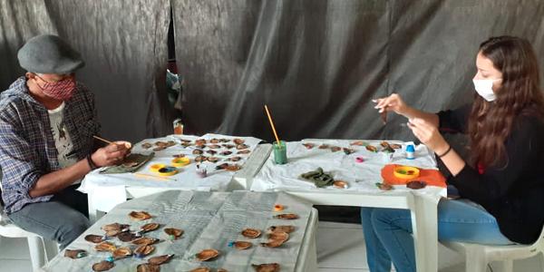 Dois jovens sentam de frente de um pro outro durante oficina de confecção de artesanato na Chácara das Flores durante a Semana dos Voluntários.