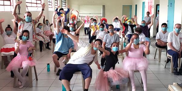 Beneficiários e colaboradores estão em pé dançando durante apresentação de show de talentos na Nova 4E durante a Semana dos Voluntários. Alguns estão fantasiados com peruca e outros assessórios.
