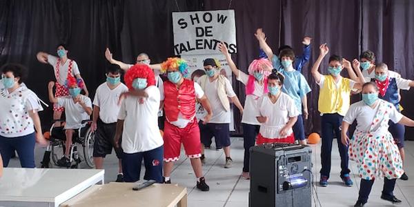 Beneficiários e colaboradores estão em pé dançando durante apresentação de show de talentos na Nova 4E durante a Semana dos Voluntários.