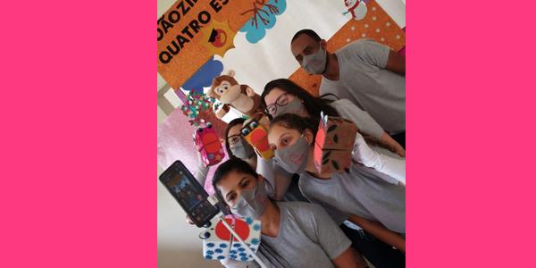 Cinco jovens seguram fantoches durante atividade na Nova 4E durante a Semana dos Voluntários.