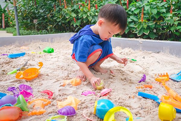 A imagem mostra uma criança brincando com objetos dentro de um tanque de areia