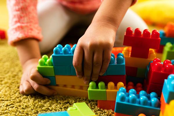 A imagem foca em duas mãos infantis manuseando blocos de montar sobre um tapete